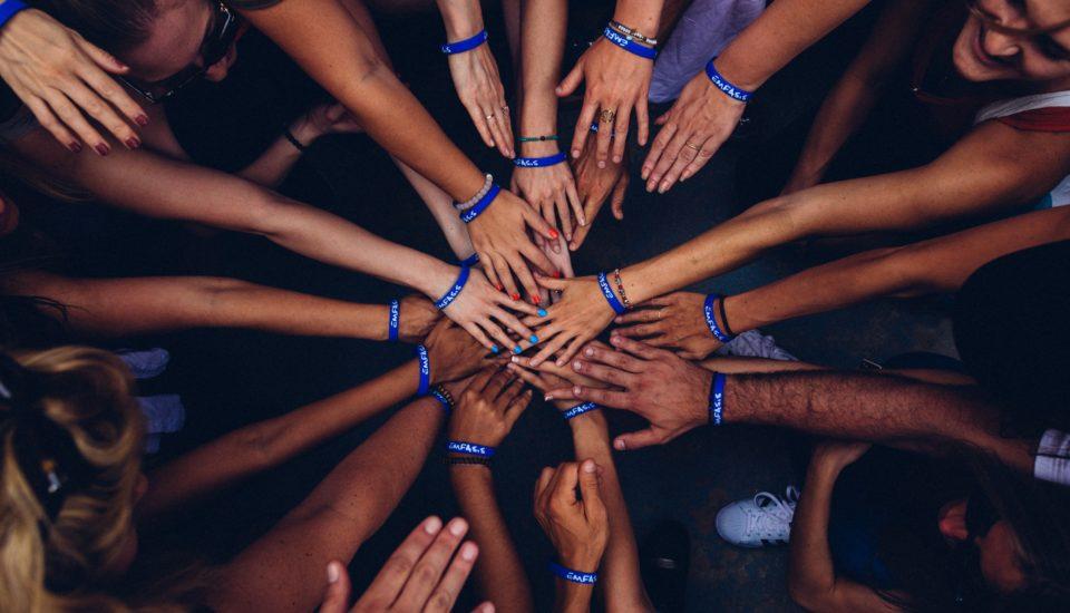Des bras et des mains qui convergent en un centre pour montrer la solidarité